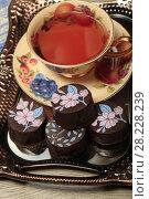 Купить «Конфеты с шоколадной глазурью и чай в красивой чашке», фото № 28228239, снято 22 марта 2018 г. (c) Яна Королёва / Фотобанк Лори