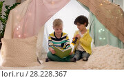Купить «happy boys reading book in kids tent at home», видеоролик № 28228367, снято 23 февраля 2018 г. (c) Syda Productions / Фотобанк Лори