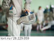 Купить «Young fencer holding foil and protective mask in his hand on the fencing tournament», фото № 28229059, снято 26 марта 2018 г. (c) Константин Шишкин / Фотобанк Лори