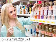 Купить «Girl choosing perfume in shop», фото № 28229571, снято 23 марта 2019 г. (c) Яков Филимонов / Фотобанк Лори