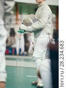 Купить «Young fencer holding rapier in his hand on the fencing tournament», фото № 28234683, снято 26 марта 2018 г. (c) Константин Шишкин / Фотобанк Лори