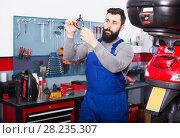 Купить «Man is observing motorbike part for fixing», фото № 28235307, снято 25 сентября 2018 г. (c) Яков Филимонов / Фотобанк Лори
