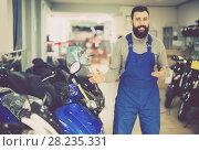 Купить «Male worker demonstrates models of motorcycles», фото № 28235331, снято 21 сентября 2019 г. (c) Яков Филимонов / Фотобанк Лори