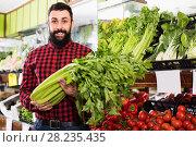 Купить «Man seller showing celery in grocery store», фото № 28235435, снято 15 ноября 2016 г. (c) Яков Филимонов / Фотобанк Лори