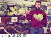Купить «Young male seller offering cauliflowers», фото № 28235451, снято 15 ноября 2016 г. (c) Яков Филимонов / Фотобанк Лори