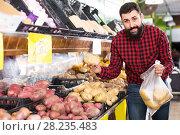 Купить «man seller showing potatoes», фото № 28235483, снято 15 ноября 2016 г. (c) Яков Филимонов / Фотобанк Лори