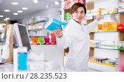 Glad female pharmacist suggesting useful drug. Стоковое фото, фотограф Яков Филимонов / Фотобанк Лори