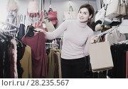 Купить «Woman buys a red blouse», фото № 28235567, снято 7 февраля 2017 г. (c) Яков Филимонов / Фотобанк Лори