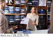 Woman seller assisting man in choosing shirt in men's cloths store. Стоковое фото, фотограф Яков Филимонов / Фотобанк Лори