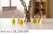 Купить «willow and candles in shape of easter eggs at home», видеоролик № 28239099, снято 28 марта 2018 г. (c) Syda Productions / Фотобанк Лори