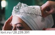 Купить «Woman tying islamic wedding turban for beautiful model», фото № 28239391, снято 5 декабря 2019 г. (c) Константин Шишкин / Фотобанк Лори