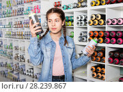 Купить «Portrait of girl choosing paint color in aerosol can in art shop», фото № 28239867, снято 12 апреля 2017 г. (c) Яков Филимонов / Фотобанк Лори
