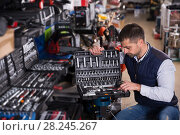Купить «male is standing with new adjustable wrench», фото № 28245267, снято 9 января 2018 г. (c) Яков Филимонов / Фотобанк Лори
