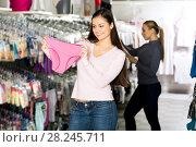 Купить «Female customer holding panties in hands», фото № 28245711, снято 10 июля 2020 г. (c) Яков Филимонов / Фотобанк Лори