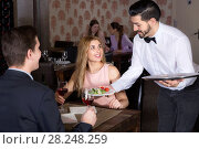Купить «Polite waiter bringing ordered dishes to smiling couple at restaurant», фото № 28248259, снято 8 января 2018 г. (c) Яков Филимонов / Фотобанк Лори