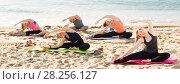 Купить «Yoga on beach, group of females training», фото № 28256127, снято 22 мая 2017 г. (c) Яков Филимонов / Фотобанк Лори
