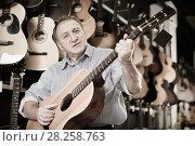 Купить «Man is playing on acoustic guitar», фото № 28258763, снято 18 сентября 2017 г. (c) Яков Филимонов / Фотобанк Лори