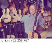 Купить «Mature man choosing acoustic guitar», фото № 28258767, снято 18 сентября 2017 г. (c) Яков Филимонов / Фотобанк Лори