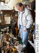 Купить «Adult man is looking old things at the fleamarket», фото № 28258843, снято 23 октября 2017 г. (c) Яков Филимонов / Фотобанк Лори