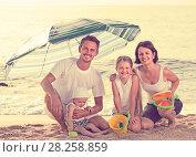 Купить «family sitting under umbrella on the beach», фото № 28258859, снято 23 апреля 2019 г. (c) Яков Филимонов / Фотобанк Лори