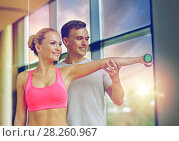 Купить «smiling young woman with personal trainer in gym», фото № 28260967, снято 29 июня 2014 г. (c) Syda Productions / Фотобанк Лори