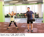Купить «man and woman with kettlebell exercising in gym», фото № 28261075, снято 19 февраля 2017 г. (c) Syda Productions / Фотобанк Лори