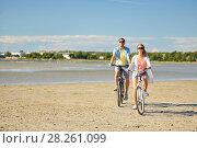 Купить «happy young couple riding bicycles at seaside», фото № 28261099, снято 23 июля 2017 г. (c) Syda Productions / Фотобанк Лори