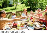 Купить «happy family having dinner or summer garden party», фото № 28261259, снято 9 июля 2017 г. (c) Syda Productions / Фотобанк Лори