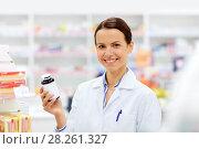 Купить «happy female apothecary with drug at pharmacy», фото № 28261327, снято 27 июня 2015 г. (c) Syda Productions / Фотобанк Лори
