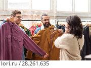 Купить «friends photographing at vintage clothing store», фото № 28261635, снято 30 ноября 2017 г. (c) Syda Productions / Фотобанк Лори