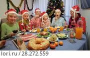 Купить «Happy family is talking at the table in time celebration New Year at home.», видеоролик № 28272559, снято 17 января 2018 г. (c) Яков Филимонов / Фотобанк Лори