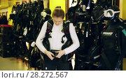 Купить «Sporty woman is trying new diving vest in the diving store.», видеоролик № 28272567, снято 13 февраля 2018 г. (c) Яков Филимонов / Фотобанк Лори