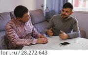 Купить «Two cheerful men enjoying conversation at home table», видеоролик № 28272643, снято 26 февраля 2018 г. (c) Яков Филимонов / Фотобанк Лори