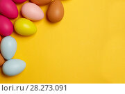Купить «Colorful Easter eggs on a yellow background», фото № 28273091, снято 17 марта 2018 г. (c) Иван Карпов / Фотобанк Лори
