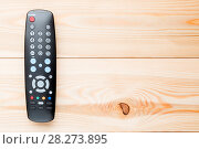 Купить «remote control for switching channels on the TV set on the wooden floor on the right», фото № 28273895, снято 23 июля 2016 г. (c) Константин Лабунский / Фотобанк Лори