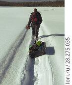 Рыбак тащит по снегу волокуши со снаряжением. Стоковое фото, фотограф Юлия Юриева / Фотобанк Лори