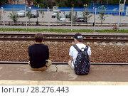 Подростки сидят на краю железнодорожной платформы (2016 год). Редакционное фото, фотограф Free Wind / Фотобанк Лори