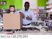 Купить «African american male with purchases box in household shop», фото № 28276991, снято 21 февраля 2018 г. (c) Яков Филимонов / Фотобанк Лори