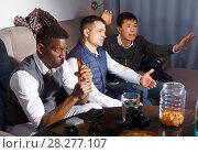 Купить «Three outraged men are watching TV and cheering for football team», фото № 28277107, снято 23 февраля 2018 г. (c) Яков Филимонов / Фотобанк Лори