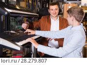 Купить «Father and teenage son examining keyboards in guitar shop», фото № 28279807, снято 29 марта 2017 г. (c) Яков Филимонов / Фотобанк Лори