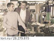 Купить «Father and teenage son examining drum units in guitar shop», фото № 28279815, снято 29 марта 2017 г. (c) Яков Филимонов / Фотобанк Лори