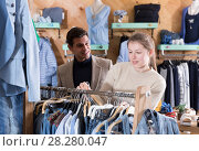 Купить «Young female with male are looking on jeans clothes on hanger», фото № 28280047, снято 12 марта 2018 г. (c) Яков Филимонов / Фотобанк Лори