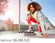 Купить «Happy African girl posing on floor at skate park», фото № 28280523, снято 14 октября 2017 г. (c) Сергей Новиков / Фотобанк Лори