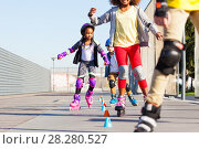 Купить «Kids learning to slalom skate with inline skates», фото № 28280527, снято 14 октября 2017 г. (c) Сергей Новиков / Фотобанк Лори