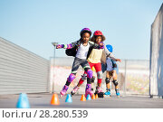 Купить «Young inline skaters doing tricks at skate park», фото № 28280539, снято 14 октября 2017 г. (c) Сергей Новиков / Фотобанк Лори