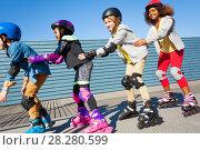 Купить «Happy friends having fun while rollerblading», фото № 28280599, снято 14 октября 2017 г. (c) Сергей Новиков / Фотобанк Лори