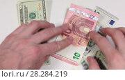 Купить «Пересчет денег в руках, евро и доллары, крупный план», видеоролик № 28284219, снято 26 февраля 2018 г. (c) Кекяляйнен Андрей / Фотобанк Лори