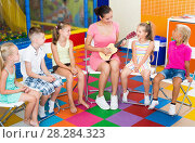 Купить «Happy children listening teacher playing small guitar», фото № 28284323, снято 18 сентября 2018 г. (c) Яков Филимонов / Фотобанк Лори