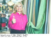 Купить «Woman seller showing curtain and holding thumb up», фото № 28292147, снято 17 января 2018 г. (c) Яков Филимонов / Фотобанк Лори