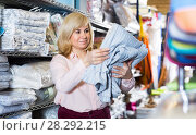 Купить «Portrait of mature woman customer picking cotton bed cover», фото № 28292215, снято 17 января 2018 г. (c) Яков Филимонов / Фотобанк Лори